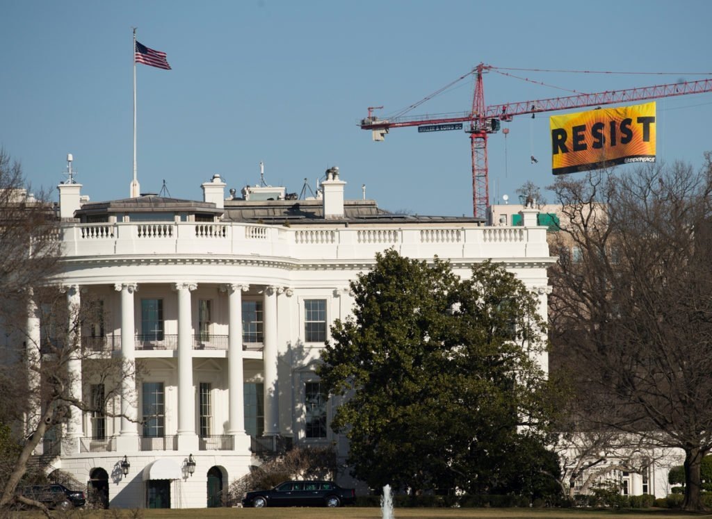 """Greenpeace activists deploy a banner on a construction crane near the White House reading """"RESIST"""" on President Trump's fifth day in office.The activists are calling for those who want to resist Trump's attacks on environmental, social, economic and educational justice to contribute to a better America."""